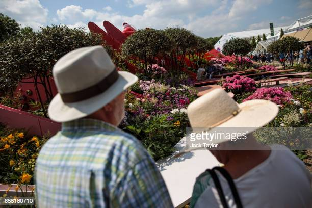 Visitors wearing sun hats look at the 'Chengdu Silk Road Garden' at the Chelsea Flower Show on May 25 2017 in London England Visitors are enjoying...