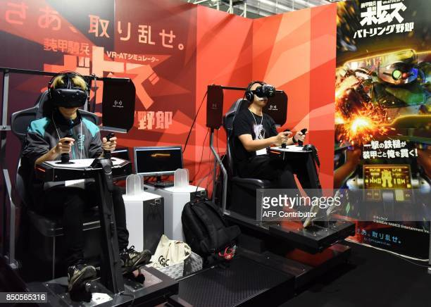 Visitors wearing virtual reality headsets try out a game at Tokyo Game Show in Chiba City, suburban Tokyo on September 21, 2017. Top eSports players...