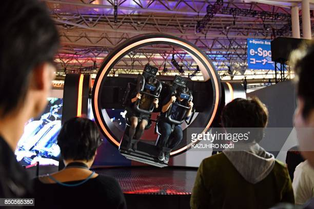 Visitors wearing virtual reality headsets try out a game at Tokyo Game Show in Chiba City suburban Tokyo on September 21 2017 Top eSports players...