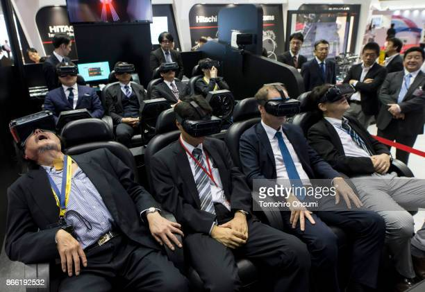 Visitors wearing virtual reality headsets try the VR Ride Theater in the Hitachi Automotive Systems Ltd booth during the Tokyo Motor Show at Tokyo...