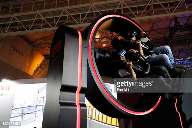 Visitors wearing VR headsets play Gyro VR Simulator in the SANGWHA booth during the Tokyo Game Show 2017 at Makuhari Messe on September 21, 2017 in...