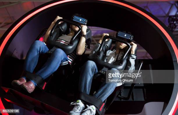 Visitors wearing VR headsets ride the Gyro virtual reality attraction during the Tokyo Game Show 2017 at Makuhari Messe on September 21 2017 in Chiba...