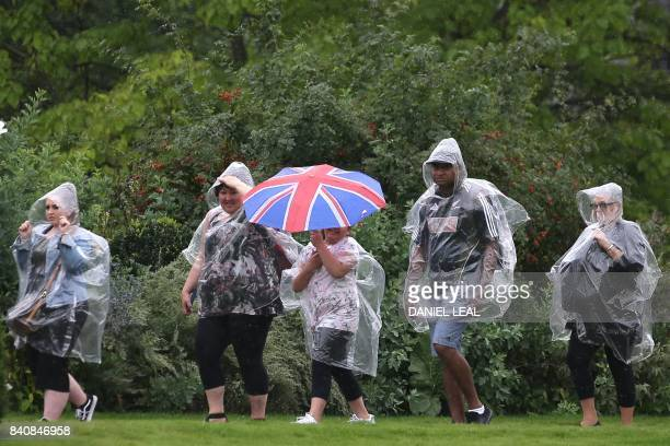 TOPSHOT Visitors with a Union Flag umbrella walk through Kensington Palace Gardens in London on August 30 2017 Britain prepares to mark the 20th...