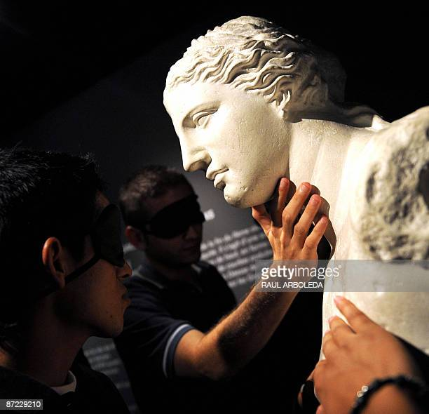 Visitors with their eyes covered touch a replica of the 'Venus de Milo' during the exhibition called 'Touch to See' with replicas of sculptures from...