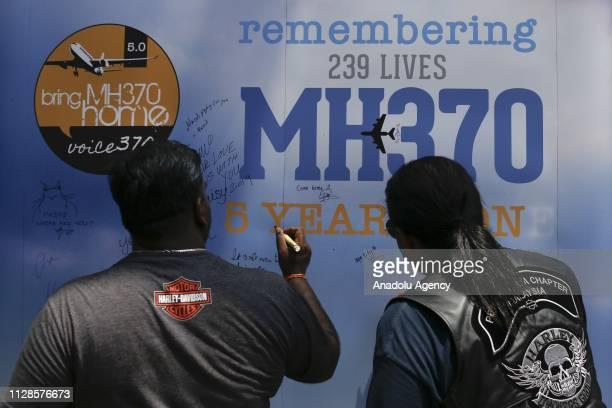 Visitors write messages on the board during a commemoration event to mark the 5th anniversary of the missing Malaysia Airlines MH370 flight in Kuala...