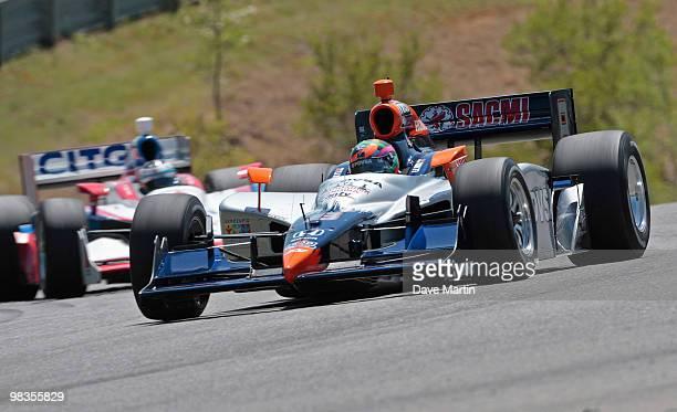 J Viso of Venezuela driver of the KV Racing Technology Dallara Honda leads Milka Duno driver of the CITGO Dallara Honda through turn one during...