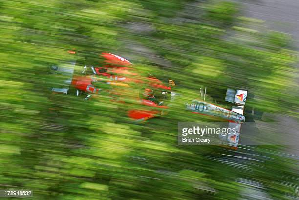 J Viso of Venezuela driver of the Team Venezuala/Andretti Autosport/HVM Chevrolet Dallara drives his car past some trees during for practice for the...