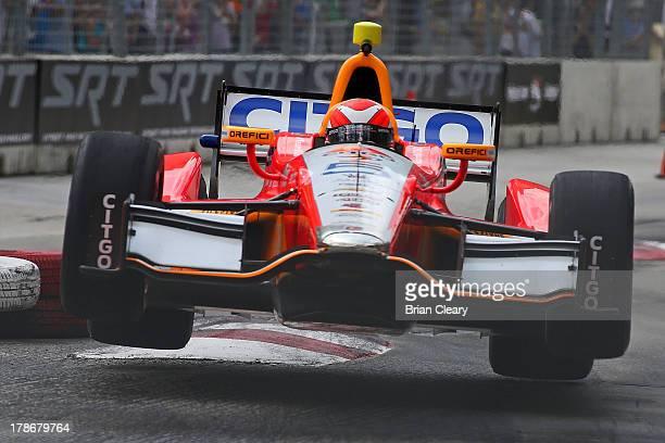 J Viso of Venezuela driver of the Team Venezuela/Andretti Autosport HVM Chevrolet Dallara races over some curbing during practice for the Grand Prix...