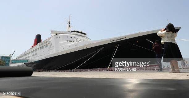 Visotors take photos of the Queen Elizabeth II luxury cruise liner also known as the QE2 docked at Port Rashid in Dubai where it will be moored...