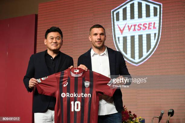 Vissel Kobe new player Lukas Podolski poses with his new jersey next to Rakuten CEO Hiroshi Mikitani during a press conference on July 6 2017 in Kobe...