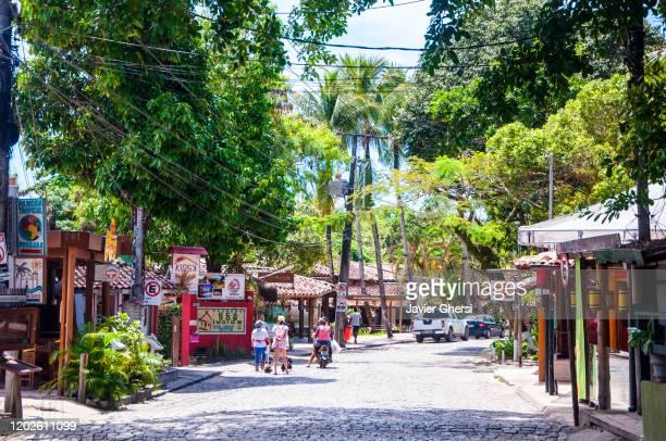 vista de la rua do mucugê y sus comercios. arraial d'ajuda, brasil. - rua stock-fotos und bilder