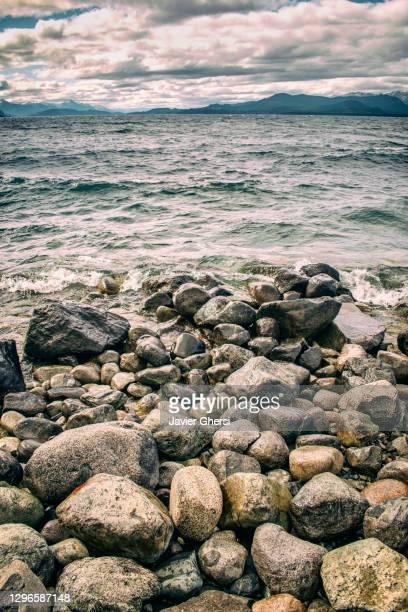 vista del lago nahuel huapi, el cielo nublado y las piedras. bariloche, río negro, argentina. - cielo stock pictures, royalty-free photos & images