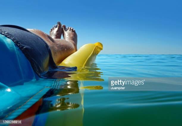 vista lateral de un hombre en una colchoneta disfrutando del mar en verano - vista lateral stock-fotos und bilder