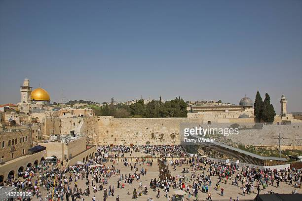Vista of crowded plaza below Jerusalem stone wall.