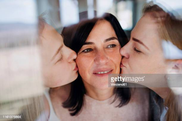 visting daughters kissing their mother, standing at the window - gratitude stock pictures, royalty-free photos & images