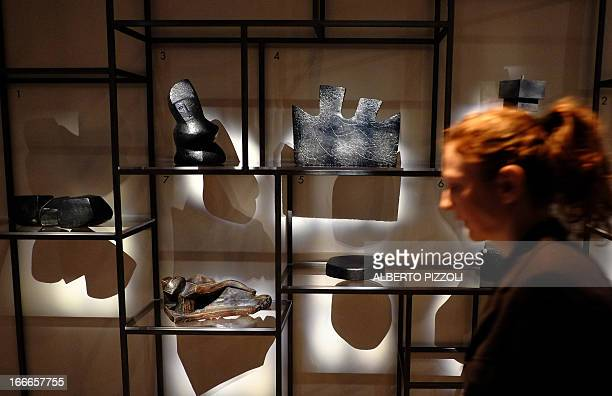 A vistor passes by sculptures by US artist Louise Nevelson during the press preview of the 'Louise Nevelson' exhibition on April 15 2013 at the...