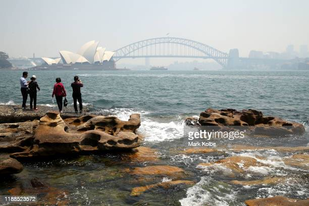 Vistors at Mrs Macquarie's Chair overlook a smoke covered Sydney Harbour on November 19 2019 in Sydney Australia NSW remains under severe or very...