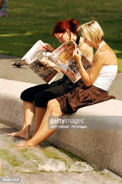 Vistors cool off their feet in the Princess Diana Memorial Fountain in Hyde Park in central London