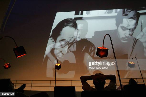 Vistors watch a video screened on the wall during an exhibition to celebrate the 50th anniversary of Brazilian movement and musical style 'Bossa...