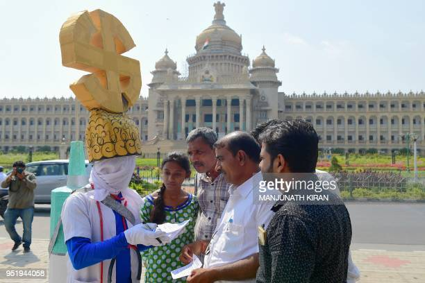 A visual artist 54yearold Parmesh Jolad wears an election symbol as he speaks with people in front of the Vidhana Soudha as part of Vote Therapy a...