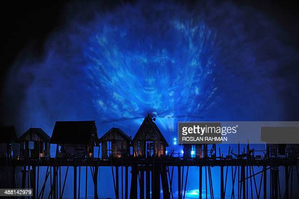 A visual display is projected during the last show of a pyrotechnic and laser display over a specially built kelong or fishing village during the...