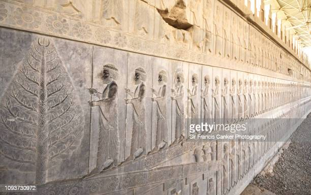 visual effect of dozens of similar persian warriors preparing to fight in persepolis, iran - bas relief stock pictures, royalty-free photos & images