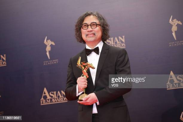 Visual effects supervisor Alex Lim HungFung poses with the trophy backstage after winning the Best Visual Effects during the 13th Asian Film Awards...