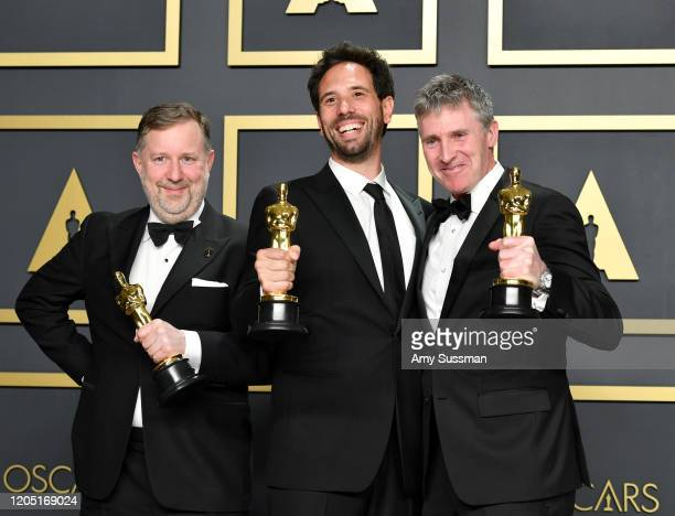 """Visual effects supervisors Guillaume Rocheron, Dominic Tuohy, and Greg Butler, winners of the Visual Effects award for """"1917,"""" pose in the press room..."""