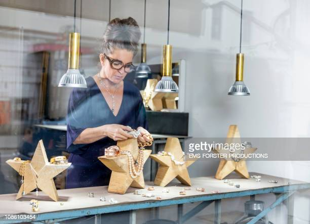 visual merchandiser decorating a jewelry store for xmas time - 宝石職人 ストックフォトと画像