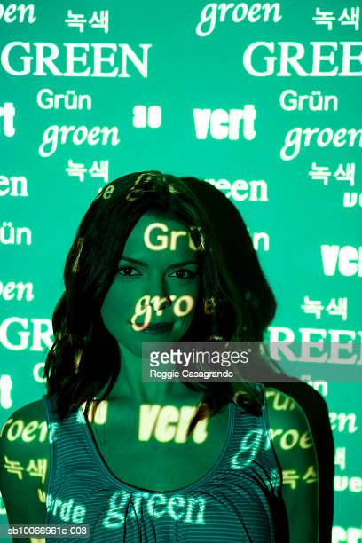 Visual projection of pattern reading green in various languages cast on woman, portrait