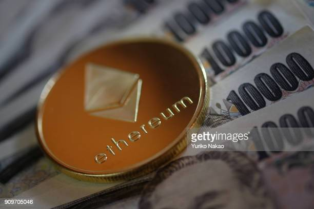 THE HAGUE NETHERLANDS JANUARY 13 2018 A visual representations of cryptocurrency Ethereum is placed on Japanese 10000 yen notes in this photo...