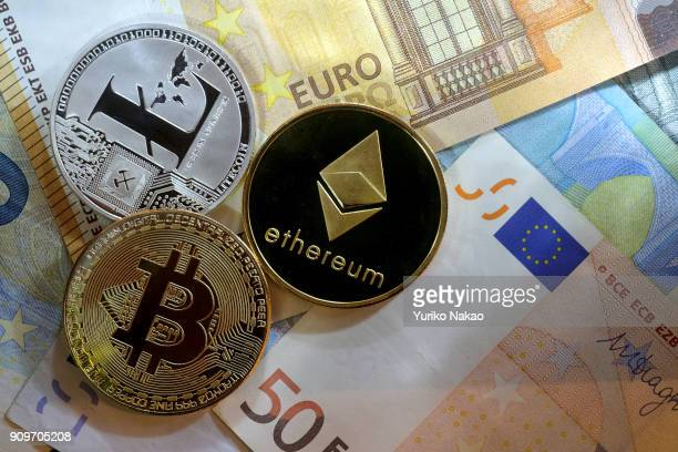 THE HAGUE NETHERLANDS JANUARY 13 2018 Visual representations of cryptocurrency Ethereum Litecoin and a Bitcoin are placed on Euro notes in this photo...