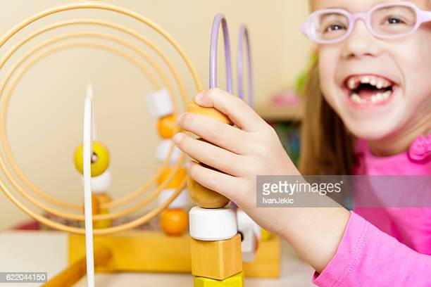 Visually disabled child playing with wooden roller coaster bead toy