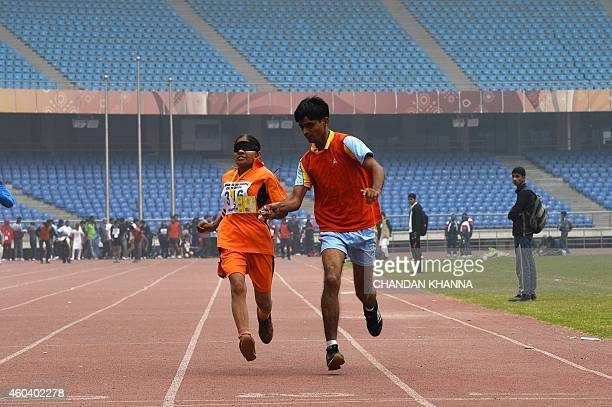 A visually impaired athlete completes the 100meter women's sprint event with a running guide during the 19th Indian Blind Sports Association National...