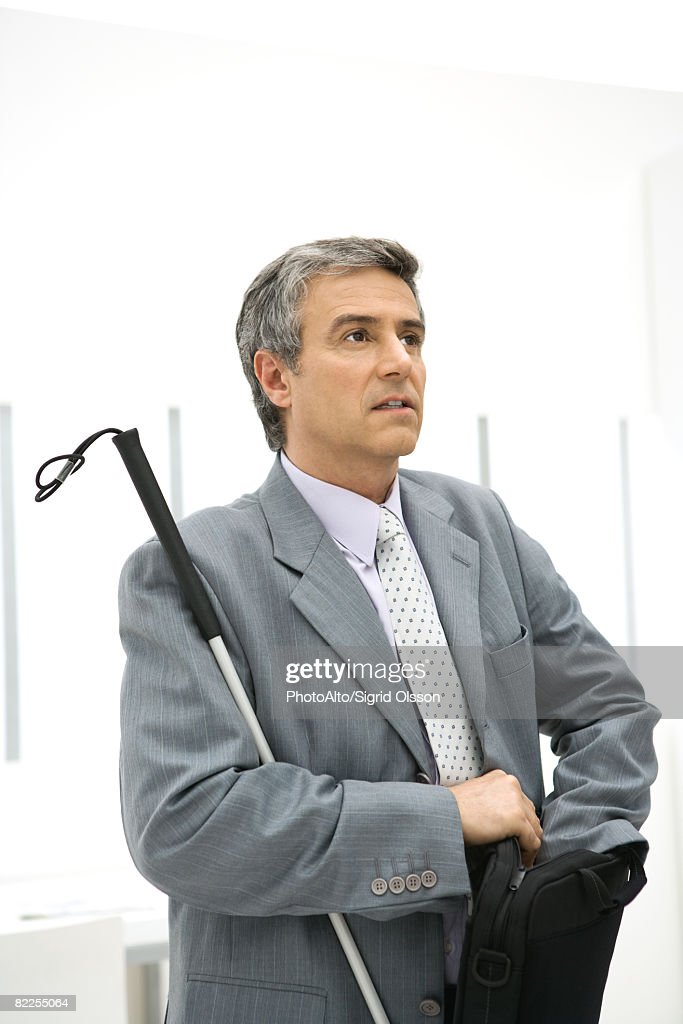 Visually impaired businessman holding white can, digging in briefcase : Stock Photo