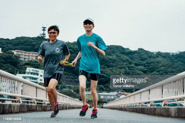 visually impaired female triathlete running together with her guide - 障害者スポーツ ストックフォトと画像