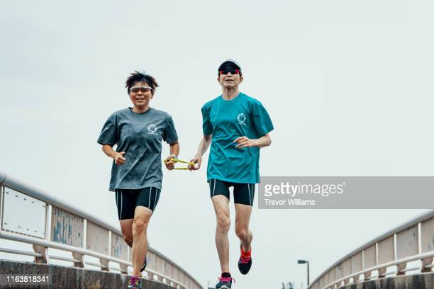visually impaired female triathlete running together with her guide - 視覚障害 ストックフォトと画像