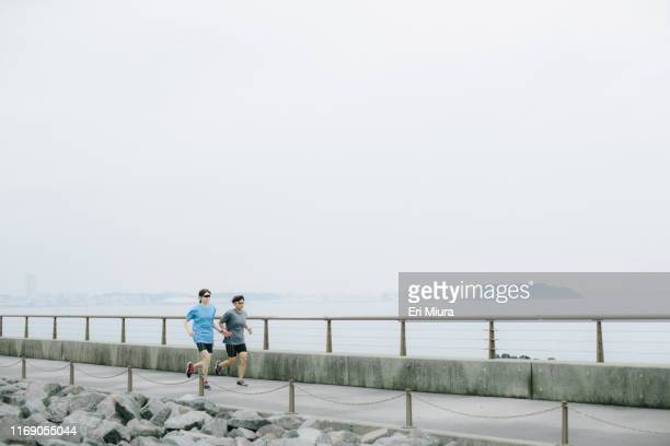 visually impaired female triathlete running together with her guide - パラリンピック選手 ストックフォトと画像