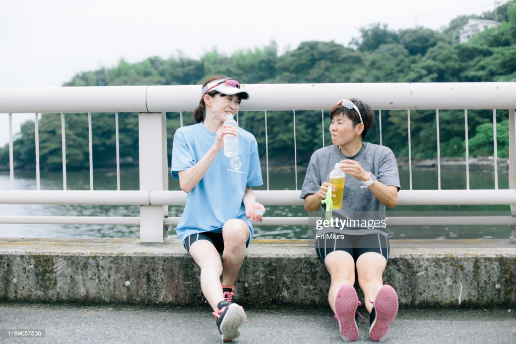 Visually impaired female triathlete taking a break from training together with her guide and coach : Stock Photo