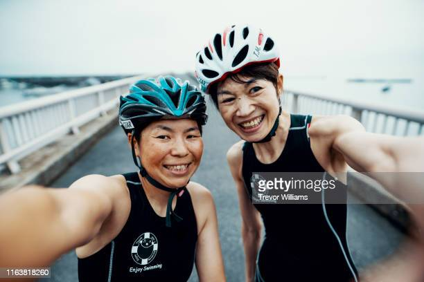 visually impaired female triathlete taking taking a selfie with her guide and coach - disabilitycollection stock-fotos und bilder