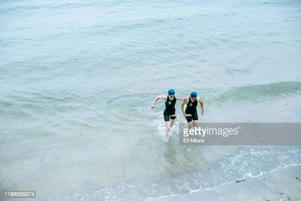 Visually impaired female triathlete with her guide coming up from the sea
