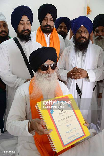 Visually impaired Indian Sikh, Gurmej Singh reads a braille copy of the Guru Granth Sahib - Sikh Holy Book - at the Sikh Shrine Golden temple complex...
