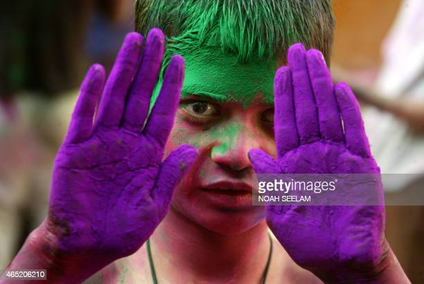 A visually impaired Indian student from The Devnar School for the Blind poses with his palms filled with coloured powders as he prepares to celebrate...