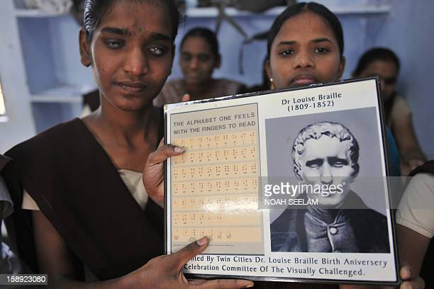 Visually impaired Indian students pose with a portrait of Louis Braille and the Braille alphabets of his invention at the Sai Junior College For The...