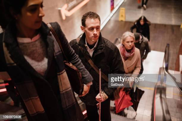 visually impaired man travelling on an escalator - blindness stock pictures, royalty-free photos & images