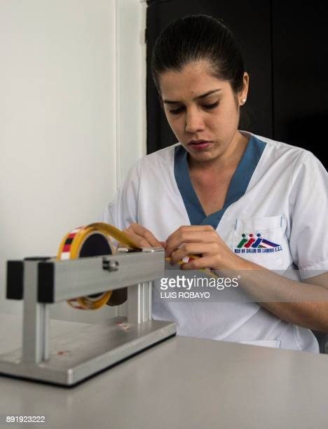 Visually impaired medical tactile examiner Leidy Garcia prepares the strips of tape marked with coordinates in Braille she uses to perform breast...