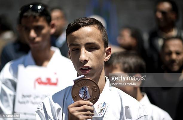 A visually impaired Palestinian youth holds a medal during a protest of the members of a blind karate team outside the Red Crescent offices in Gaza...
