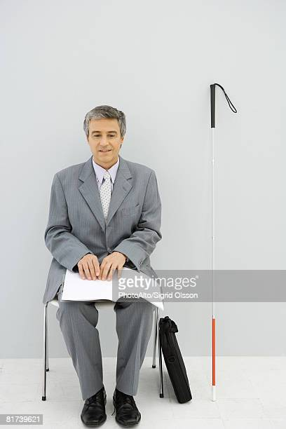 Visually impaired professional man, sitting in chair, reading Braille