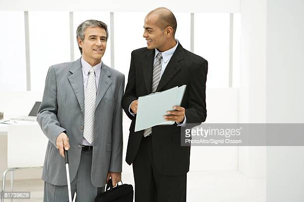 Visually impaired professional with associate, discussing documents