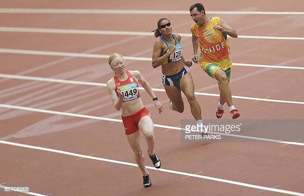 Visually impaired runner Ana Tercia Soares of Brazil is given instructions by her guide as Eva Ngui of Spain leads her in a heat of the women's 100m...